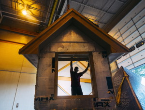 Todd Truman, owner of Turn Key Homes, loads the dormer to the Cape Cod-style house that PATHS carpentry students built. The house was taken to Durham, where its new owners will live.