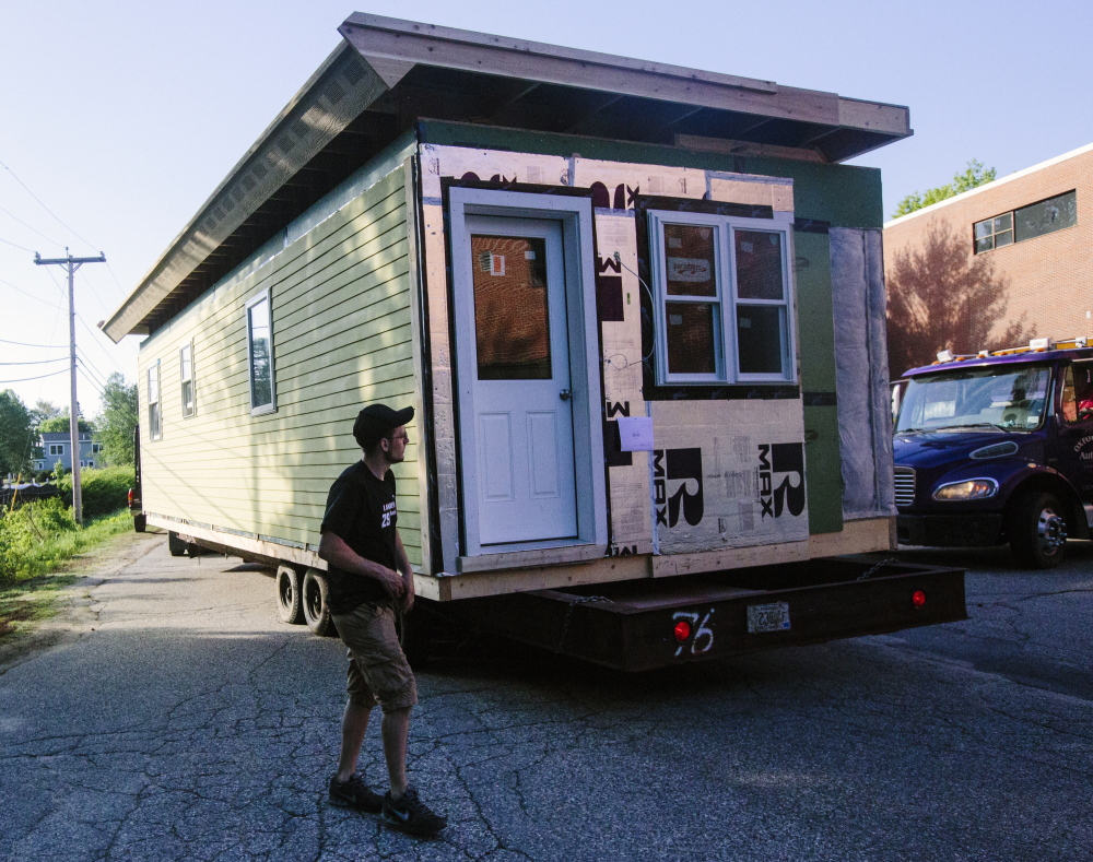Kyle Hewins from Turn Key Homes walks around the modular home that PATHS carpentry students constructed, as it is loaded onto a trailer to be transported to Durham.