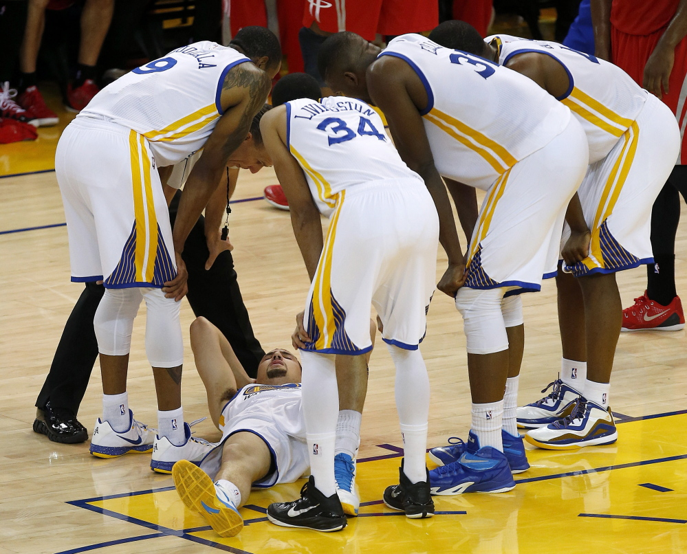 Warriors guard Klay Thompson is checked on by teammates after taking a knee to his head Wednesday. It was later determined that Thompson had sustained a concussion.