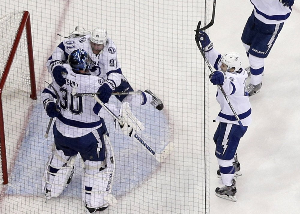 The Tampa Bay Lightning rush to embrace goalie Ben Bishop after their 2-0 win over the New York Rangers in Game 7 of the Eastern Conference finals at Madison Square Garden.