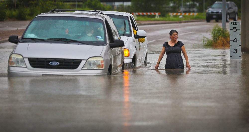 A city of Brownsville vehicle pushes a stranded van that attempted to make it through the high waters as a woman walks alongside Thursday. The Associated Press