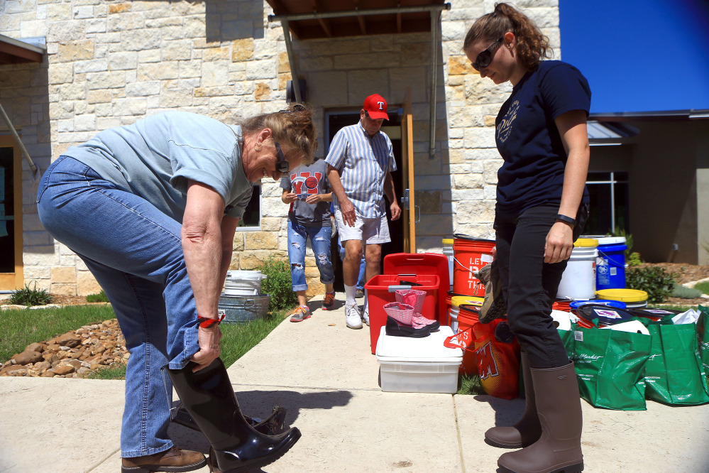 Volunteers Diana Harlien, left, and Rebecca Rippy from Austin try on boots to prepare to help residents clean their homes Friday at the Cypress Creek Church in Wimberley, Texas.