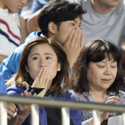 Japanese soccer fans react to a strong earthquake as they watch a J-League soccer match between the Shonan Bellmare and the Sanfrecce Hiroshima at BMW Stadium in Hiratsuka, southwest of Tokyo Saturday.
