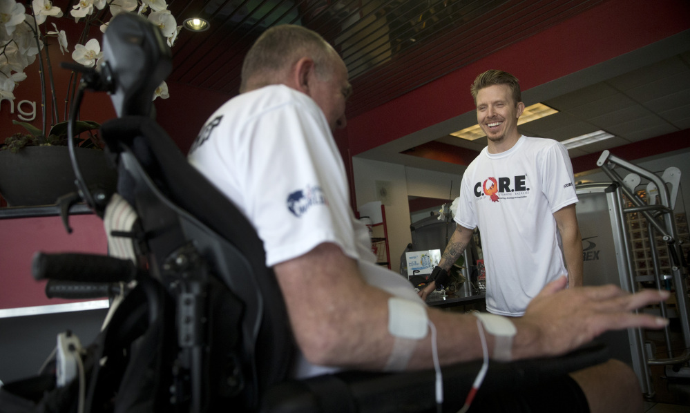 Aaron Baker, right, talks to a client at the Center for Restorative Exercise, a gym he co-founded for people recovering from spinal-cord and other debilitating injuries.