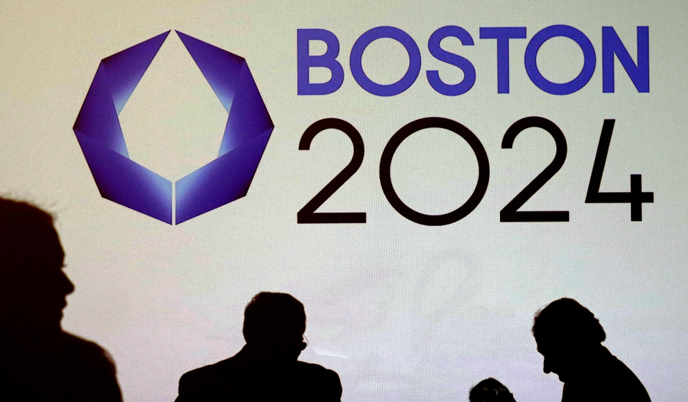 Shadows of organizers and reporters pass a video display screen prior to a January news conference by organizers of Boston's campaign for the 2024 Summer Olympics in Boston.