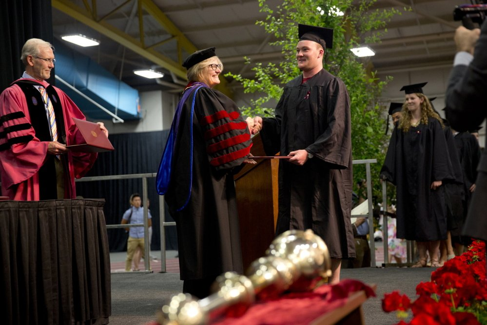Bates President Clayton Spencer hands out a diploma.