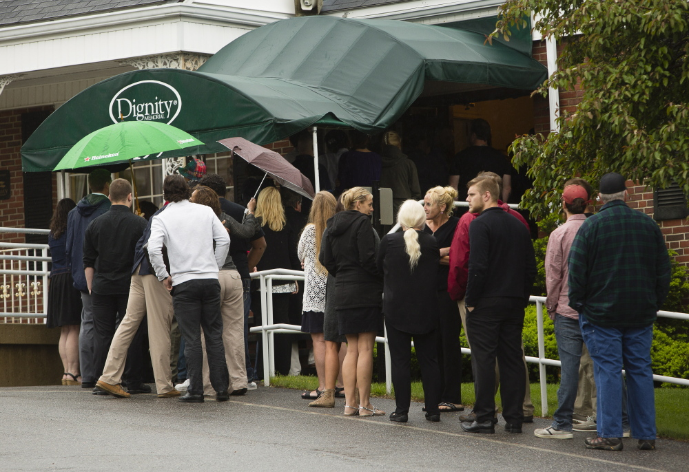 Mourners wait in a line that extended out the door at the wake Sunday.