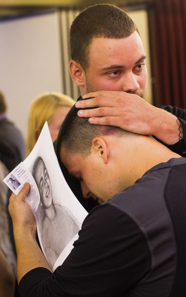 Cody Champagne and Justin Baratta, both of Westbrook, embrace in sadness at the wake of their friend Treyjon Arsenault.