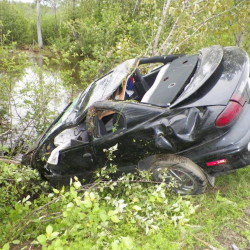Photo courtesy of Maine State Police Police say Dustin Smith was fleeing from a crime scene when he crashed this car and was pinned under it. Smith faces several charges including aggravated assault.