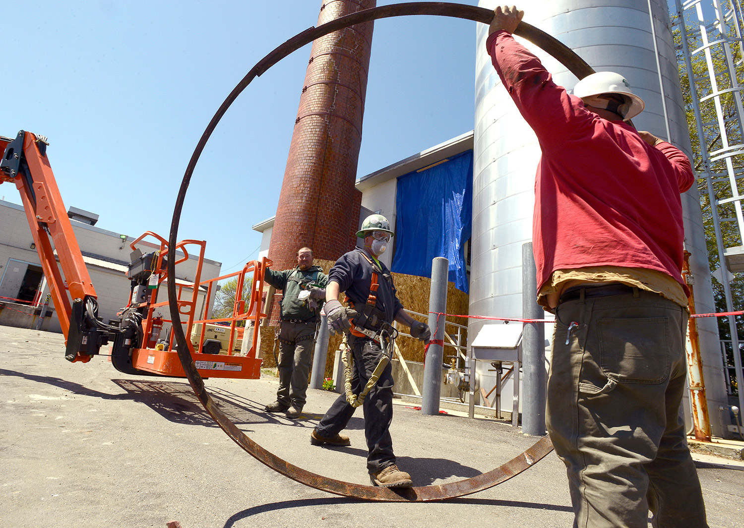 Joey Grenier and Dennis Hutchins from Tri-Stone Co. in Richmond hand off one of more than a dozen metal bands to Robert Mason as they dismantle a 105-foot-tall brick chimney attached to a old boiler plant at the University of Southern Maine campus in Portland.