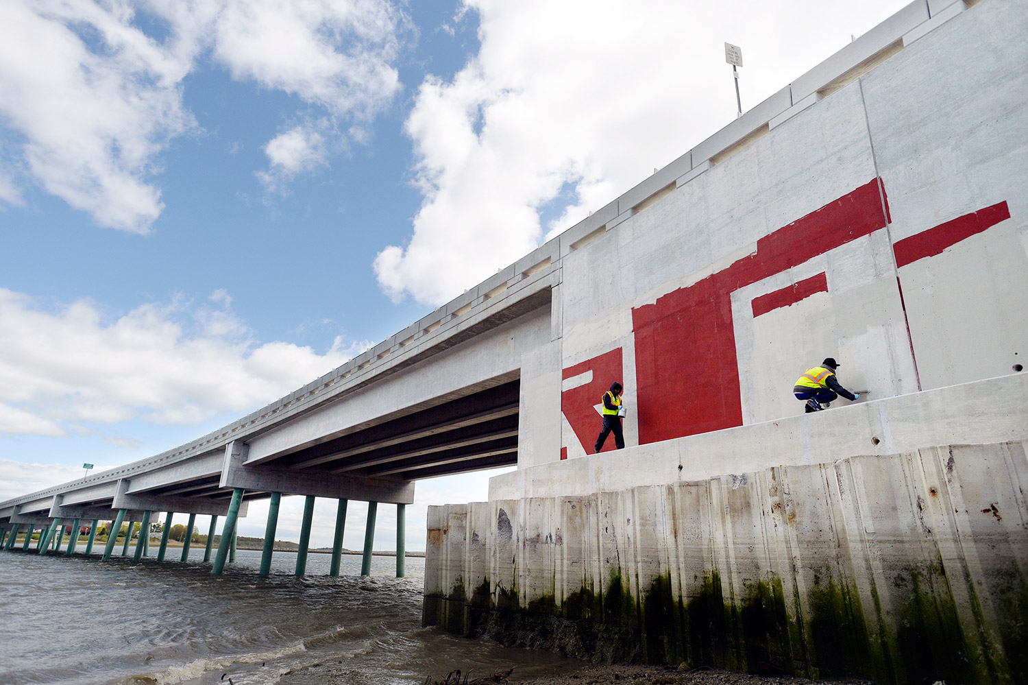 Kane and Lewis navigate their way along the side of the Martin's Point Bridge where the concrete was tagged with red paint. Youth Building Alternatives is a nationally accredited educational program that works with young men and women who have dropped out of high school.