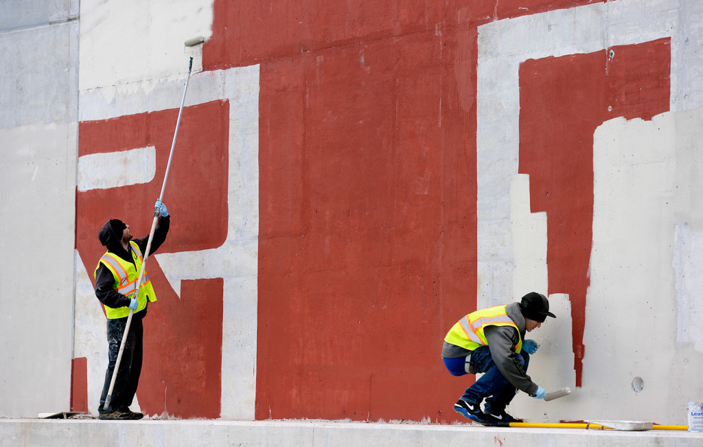 Tom Kane, left, and Caleb Lewis of Graffiti Busters work together to clean up graffiti on the Martin's Point Bridge in Falmouth. The program will receive an infusion of money from CBRE, a real estate company.
