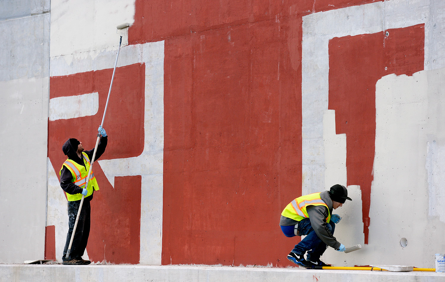 Tom Kane, left, and Caleb Lewis of Graffiti Busters work together to clean up graffiti on the Martin's Point Bridge Wednesday in Falmouth. Kane is the director of student development at Youth Building Alternatives and Lewis is a student with the program.
