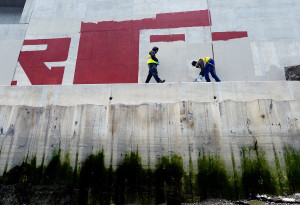PORTLAND ME - MAY 13: Tom Kane and Caleb Lewis of Graffiti Busters work together to clean up graffiti on the Martin's Point Bridge Wednesday, May 13, 2015. Kane is the director of student development at Youth Building Alternatives and Lewis is a student at Youth Building Alternatives.