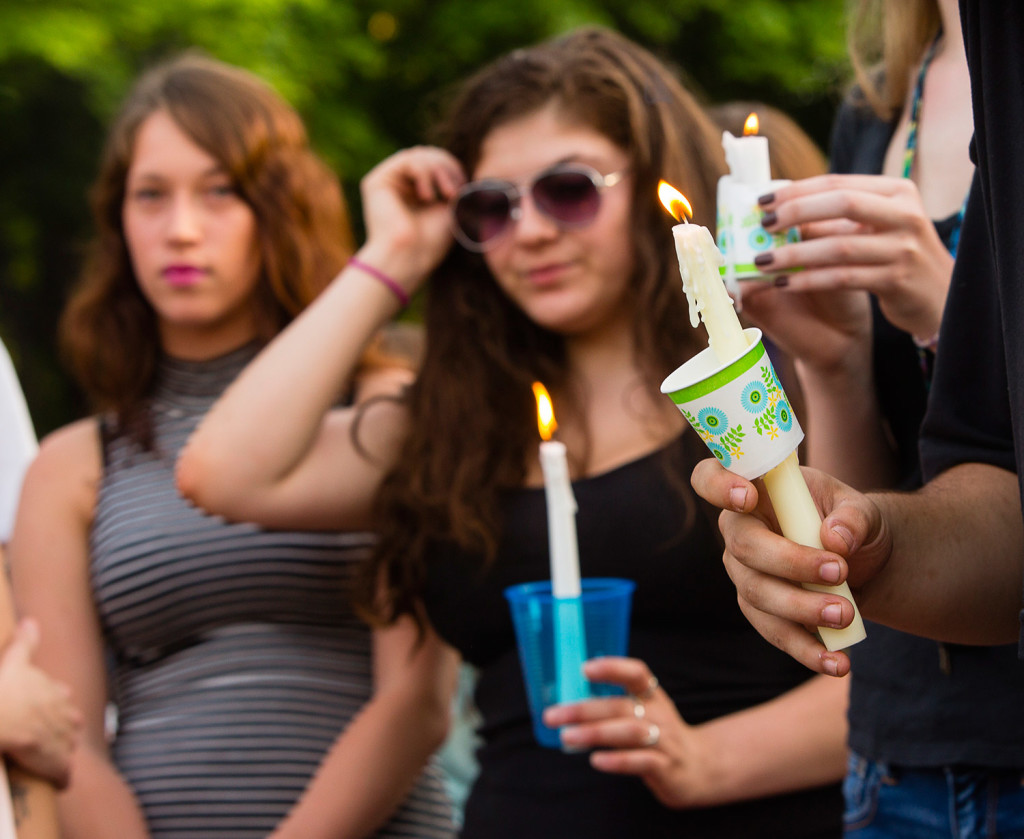 Mourners hold candles in memory of Treyjon Arsenault, a Westbrook High School graduate who was shot to death early Tuesday morning.