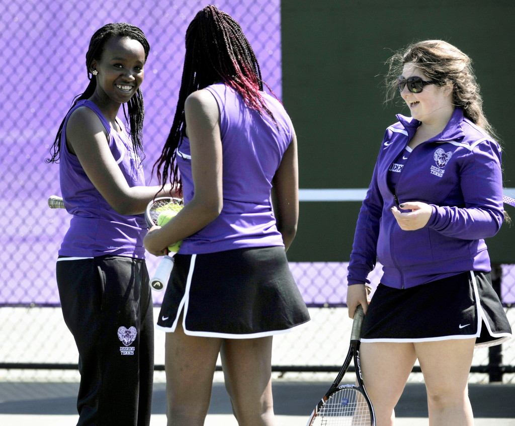 Domingas Nzuzi, left, of Angola, Gemima Masangu, center, of the Democratic Republic of Congo, and Cassi Bigelman of the Cayman Islands are part of Deering's diverse tennis team. Katie Ewald photo