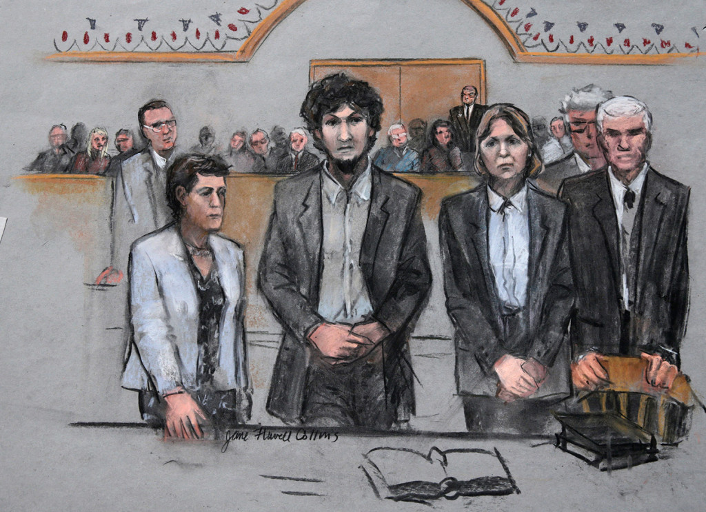In this courtroom sketch, Boston Marathon bomber Dzhokhar Tsarnaev, center,  stands with his defense attorneys as a death by lethal injection sentence is read at the Moakley Federal Court House in Boston on Friday.