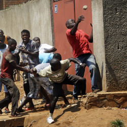 Protesters throw stones at police during clashes in Bujumbura, Burundi.