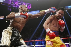 Floyd Mayweather Jr., left, hits Manny Pacquiao during their welterweight title fight Saturday in Las Vegas. The Associated Press