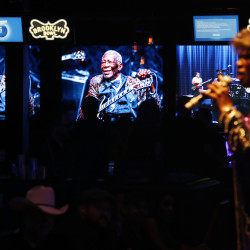 Pictures of B.B. King are displayed on a screens as Shirley King, the eldest daughter of B.B. King, performs Friday, May 22, 2015, in Las Vegas. Shirley King hosted and performed at a free musical event at the Brooklyn Bowl. (AP Photo/John Locher)