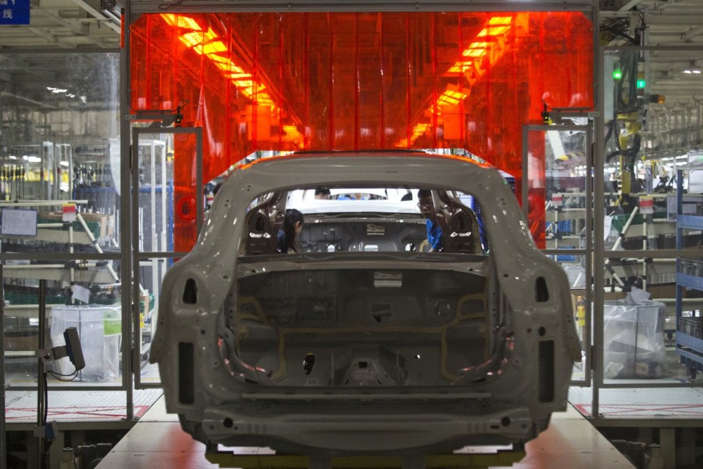 "A worker examines the metal frame of a car at a Volvo assembly line in Chengdu in southwestern China's Sichuan province. In addition to building a plant in South Carolina, the company is on the verge of exporting the first ""Made in China"" cars to the United States. The Associated Press"