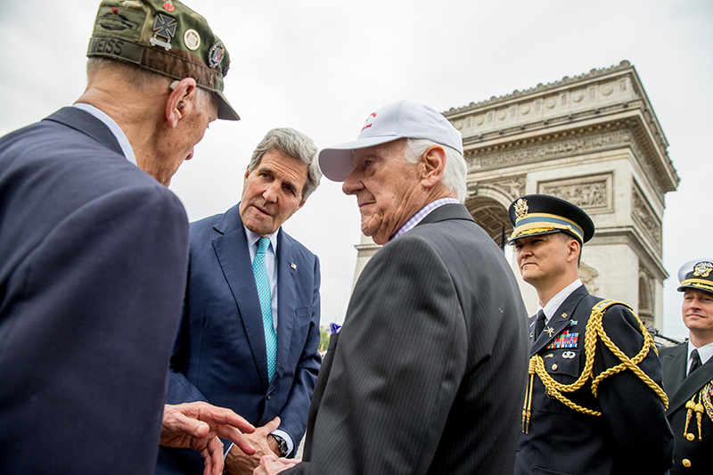 U.S. Secretary of State John Kerry greets American World War II veterans Arthur Staymates, 89, left, and Stephen Weiss, 90, center, following a wreath laying ceremony at the Tomb of the Unknown Soldier in Paris during France's 70th anniversary of V-E Day.