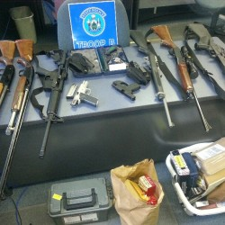 Maine State Police seized 10 guns Tuesday from a Gray man who is prohibited from owning them as a convicted felon.
