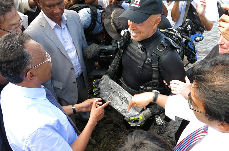 Underwater explorer Barry Clifford, right, presents a silver bar he believes is part of the treasure of the pirate Captain Kidd, to the president of Madagascar, Hery Rajaonarimampianina, left, on Sainte Marie Island, Madagascar.