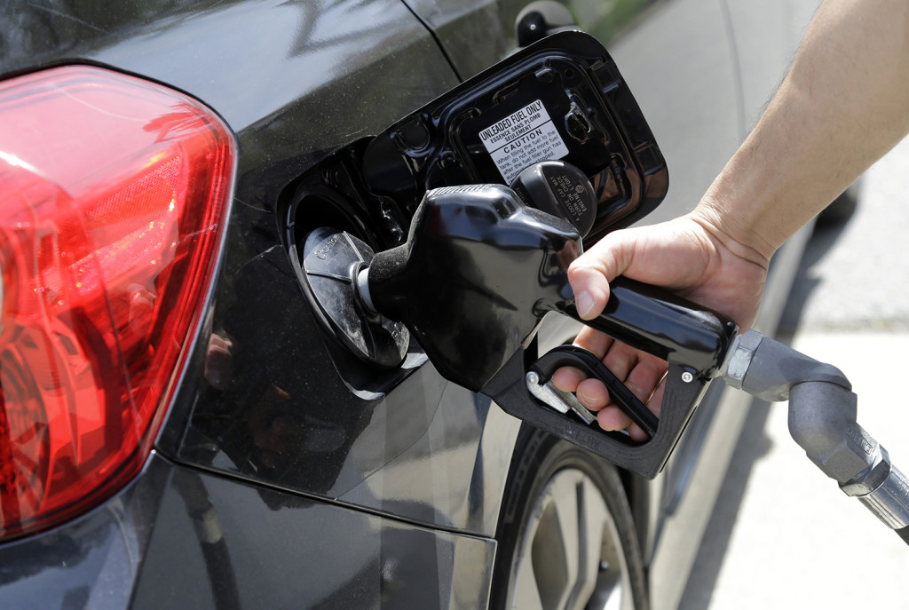 Gas station attendant Carlos Macar pumps gas Friday in Andover, Mass. The Associated Press