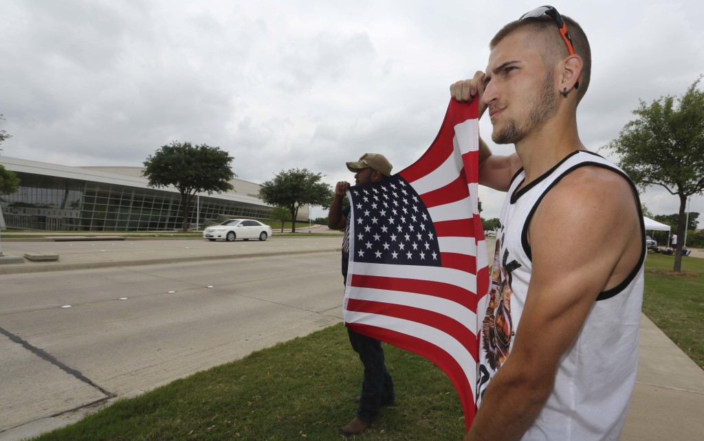 Conner McCasland, right, and Joseph Offutt hold a U.S. flag Tuesday across the street from the Curtis Culwell Center in Garland, Texas, where two suspects were killed Sunday. The Islamic State claimed responsibility for the attack.