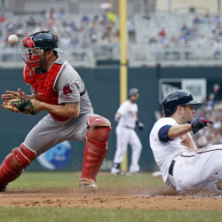 Minnesota's' Brian Dozier slides past Red Sox catcher Blake Swihart during the Twins' 7-2 win Monday.  The Associated Press