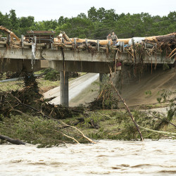 A large tree rests on the Highway 12 bridge over the Blanco River in Wimberley, Texas, where eight people are still missing after a vacation home they were staying in was swept away by raging flood waters.
