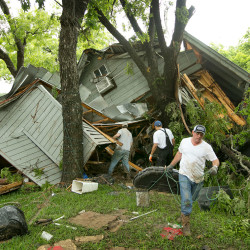 Jeremy Steele, from left, Ric Jaime and Keith McNabb salvage belongings at a friend's house near Wimberley, Texas, on Sunday. About 350 homes in the town were washed away by flash floods along the Blanco River, which rose 26 feet in one hour and left piles of wreckage 20 feet high, authorities said.  The Associated Press