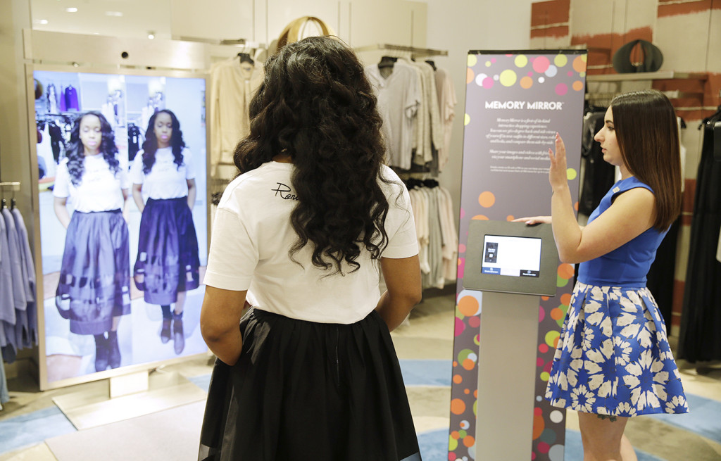 Sales manager Alysa Stefani, right, demonstrates the Memory Mirror for co-worker Porsche Colbert at the Neiman Marcus store in San Francisco's Union Square. The mirror is outfitted with sensors, setting off motion-triggered changes of clothing. The mirror also doubles as a video camera, capturing a 360-degree view of what an outfit looks like and making side-by-side comparisons. The Associated Press