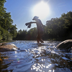 BOWDOIN COLLEGE GRANT EAST, ME - AUGUST 18: Emily Kallin carries her shoes across a stream while hiking with her family at Gulf Hagas, a registered national landmark along the Appalachian Trail corridor.  The Dresden family started out on the AT in Georgia in April and hopes to finish atop Mount Katahdin at the beginning of October. (Photo by Derek Davis/Staff Photographer)