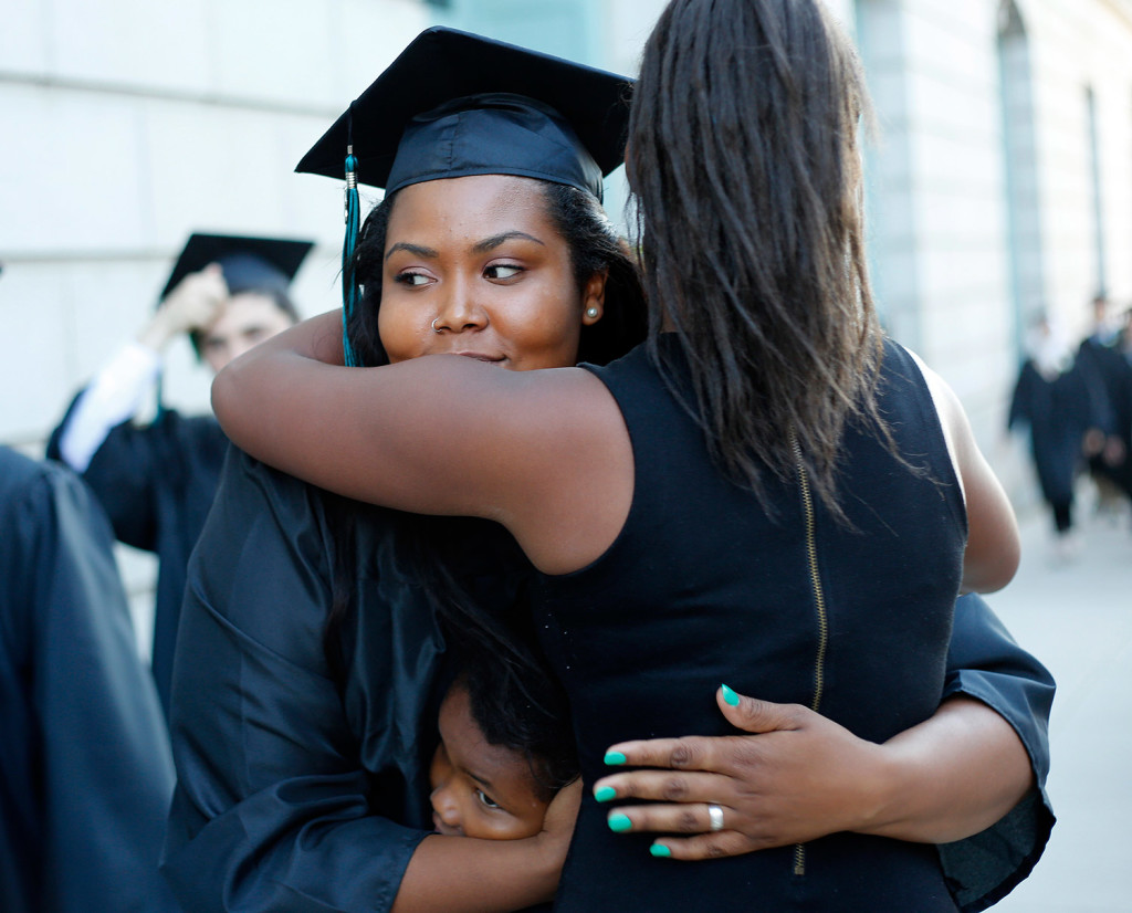 Zahara Monydet gets quick hugs from family members as she makes her way into the Merrill Auditorium for Casco Bay High School's graduation.