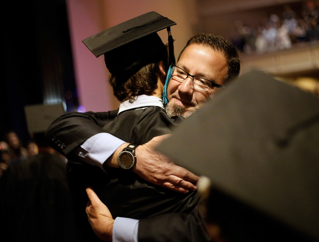 Scott Shibles, a wellness teacher and director of student life at Casco Bay High School, embraces graduates as they enter Portland's Merrill Auditorium for graduation.