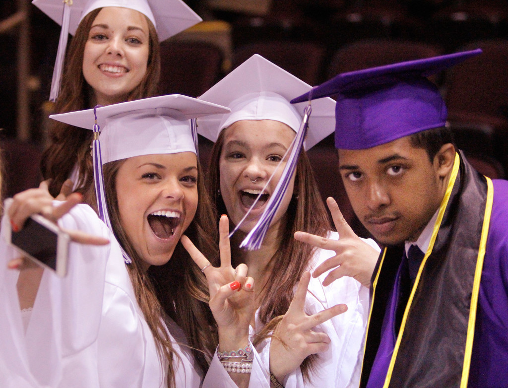 Meghan Connolly, Kayla Baldwin, Kerry Bell, left to right in front, and Nicole Labbe, rear, strike a pose while waiting for Deering High School's graduation to start at the Cross Insurance Arena in Portland on Wednesday.