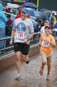 Rob Brooks of Portland  approaches the finish line of the Portland Sea Dogs Father's Day 5K with his daughter, Annabelle, 10, on Sunday. Jill Brady/Staff Photographer