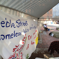 William Higgins, Jr. and Carol Kulesza sit near a canopy with banners for the Homeless Voices for Justice. Advocates and volunteers for the organization sat in Post Office Park from sunrise to sunset to mark the 8th annual Longest Day of Homelessness Summer Solstice Vigil.