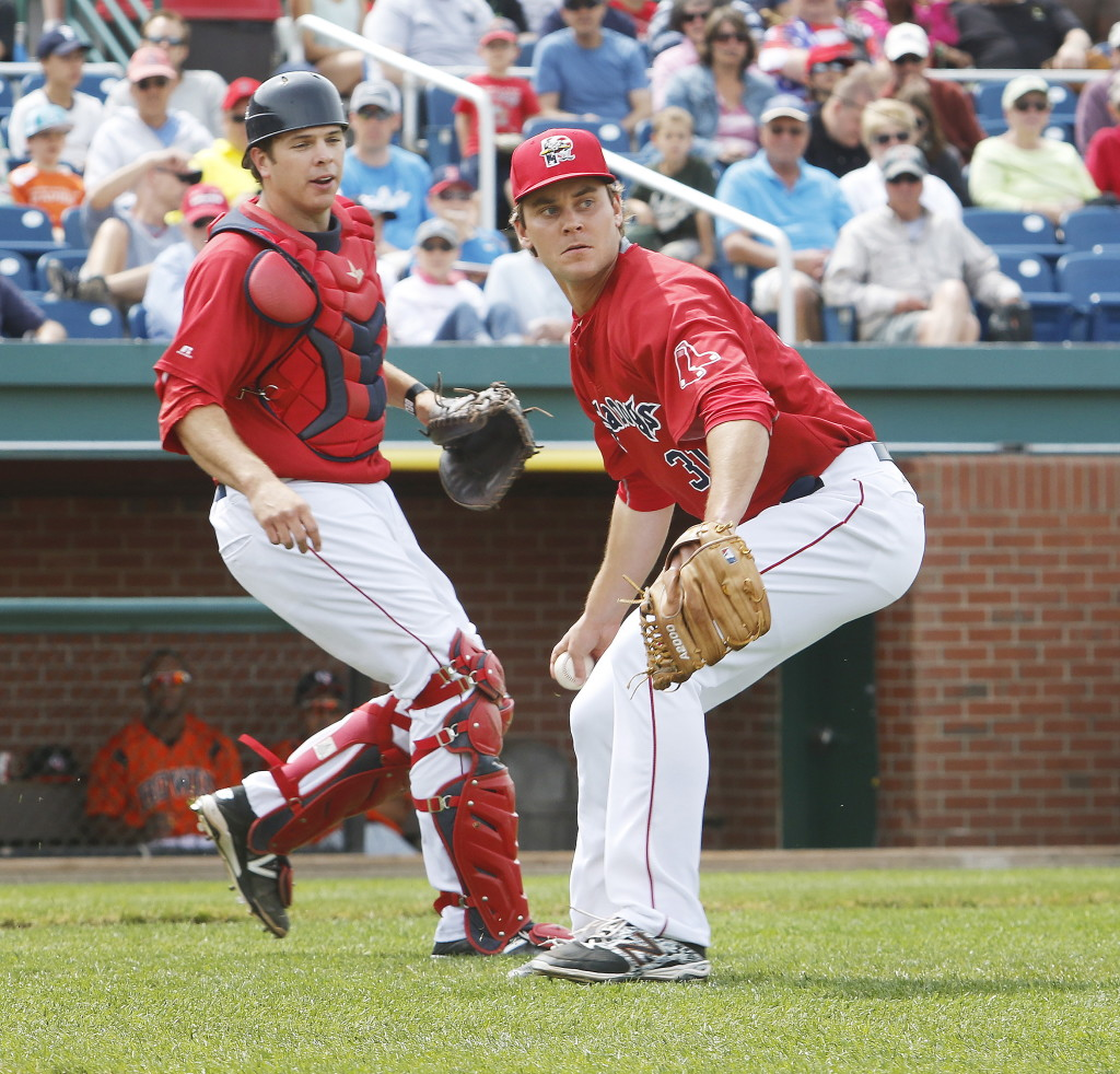 Sea Dogs reliever Madison Younginer gets ready to throw to first base for an out after fielding a ground ball while catcher Tim Roberson looks on Sunday at Hadlock Field. Jill Brady/Staff Photographer