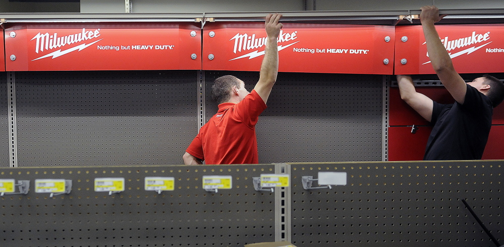 Vendors hang a tool display at Randolph Hardware on Tuesday in Randolph.