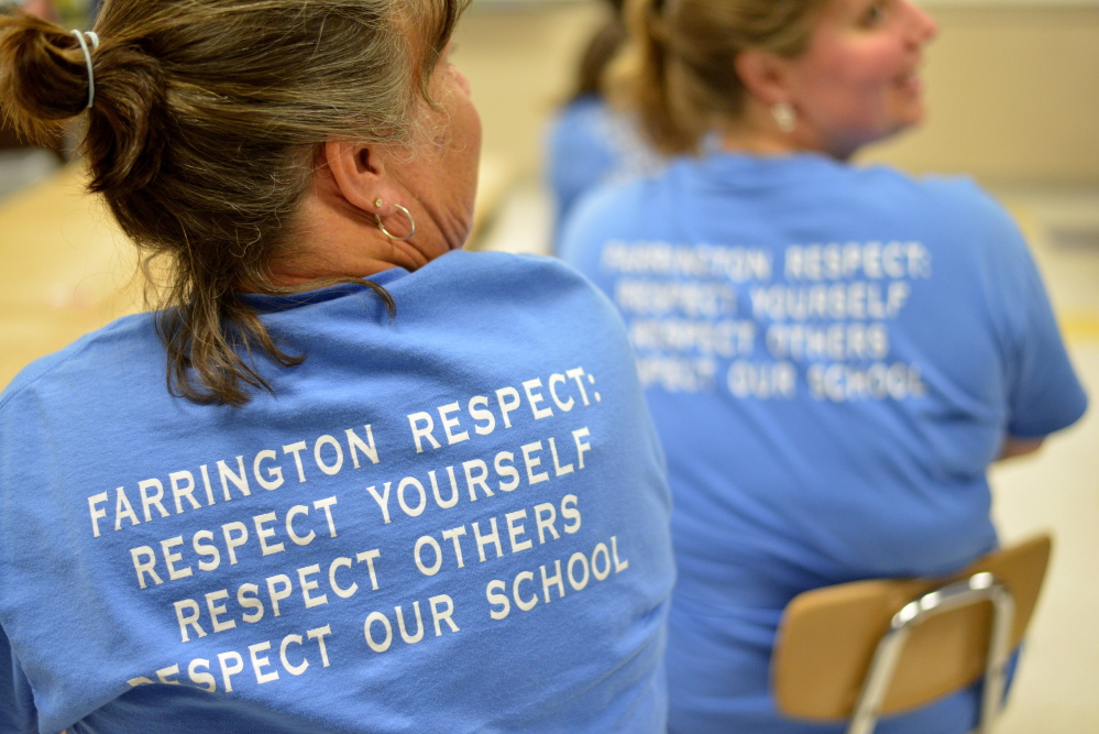 Teachers wear T-shirts in support of their school Tuesday during a news conference held at Farrington Elementary School in Augusta to address allegations that Farrington teachers left posters on the wall that offered assistance to students during standardized testing.