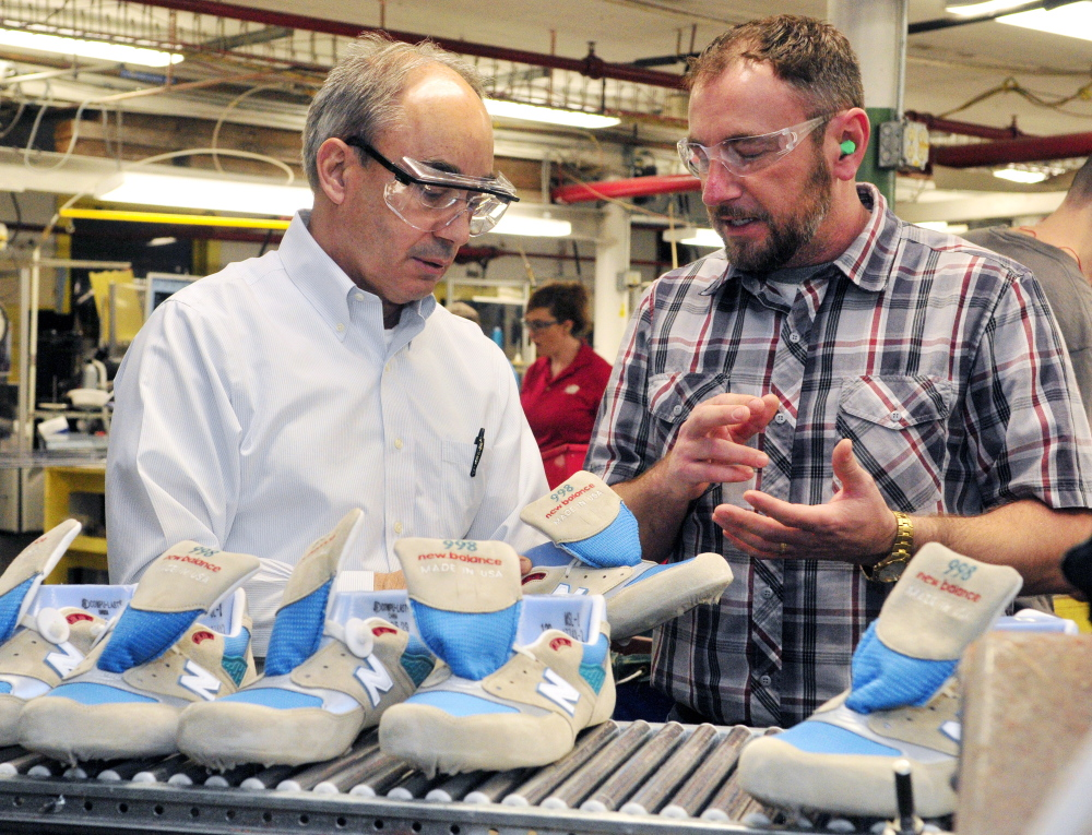 U.S. Rep. Bruce Poliquin, left, and plant manager Chuck Campbell discuss shoes April 10 during a tour of the New Balance factory in Norridgewock. New Balance officials say they have reservations, but are cautiously optimistic after the Senate passed fast track legislation Wednesday that will give the president more authority over trade deals.