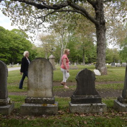 Jessica Siraco, left, executive director of the Friends of Evergreen Cemetery, and Sue Devine, a member of the group, give a tour of the park where some key players in the Portland Rum Riot of 1855 are buried.