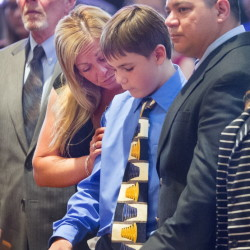 Treyjon Arsenault's mother, Nancy Laxson, comforts her son Ashton Laxson, 11, during the funeral service Monday at St. Maximilian Kolbe Church in Scarborough. At left is Nancy's father, John Arsenault, and at right is her husband, Donald Laxson, Trey's stepfather.