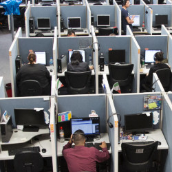 Workers sit at desks at Firstkontact Center, a call center in the northern border city of Tijuana, Mexico.