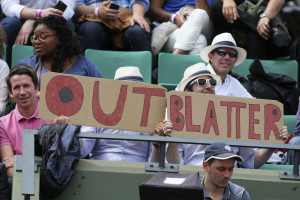 """Spectators at the French Open tennis tournament hold signs Tuesday reading """"Out Blatter,"""" referring to FIFA President Sepp Blatter, who said Tuesday that he will resign from his position in the midst of a corruption investigation."""