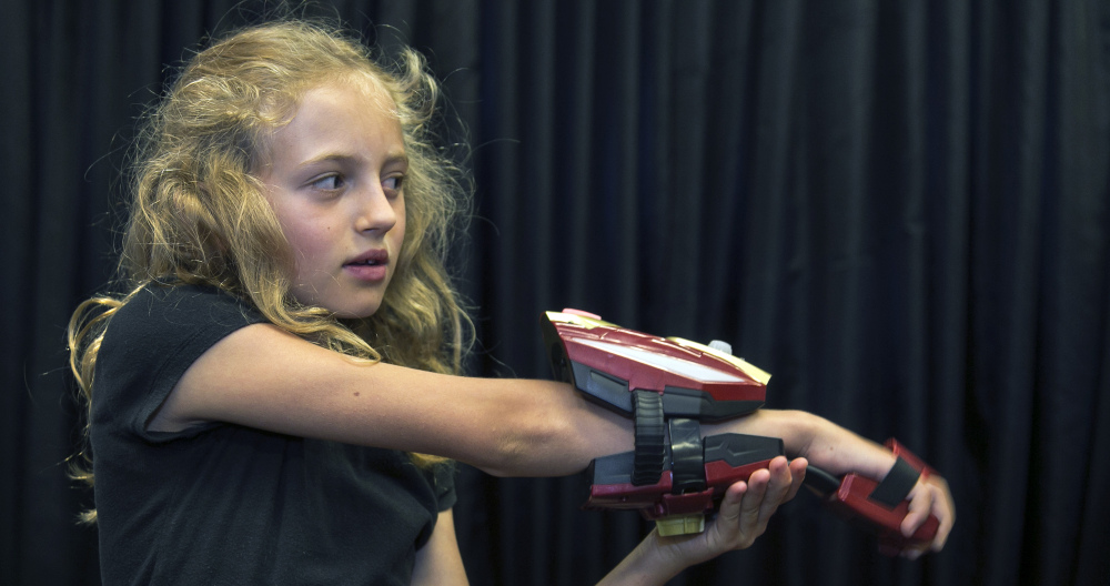 "Evangeline Lindes demonstrates a ""repulsor,"" a wearable forearm attachment with infrared and other sensors that puts kids in the role of Marvel superhero Iron Man as part of Disney's new line of toys."