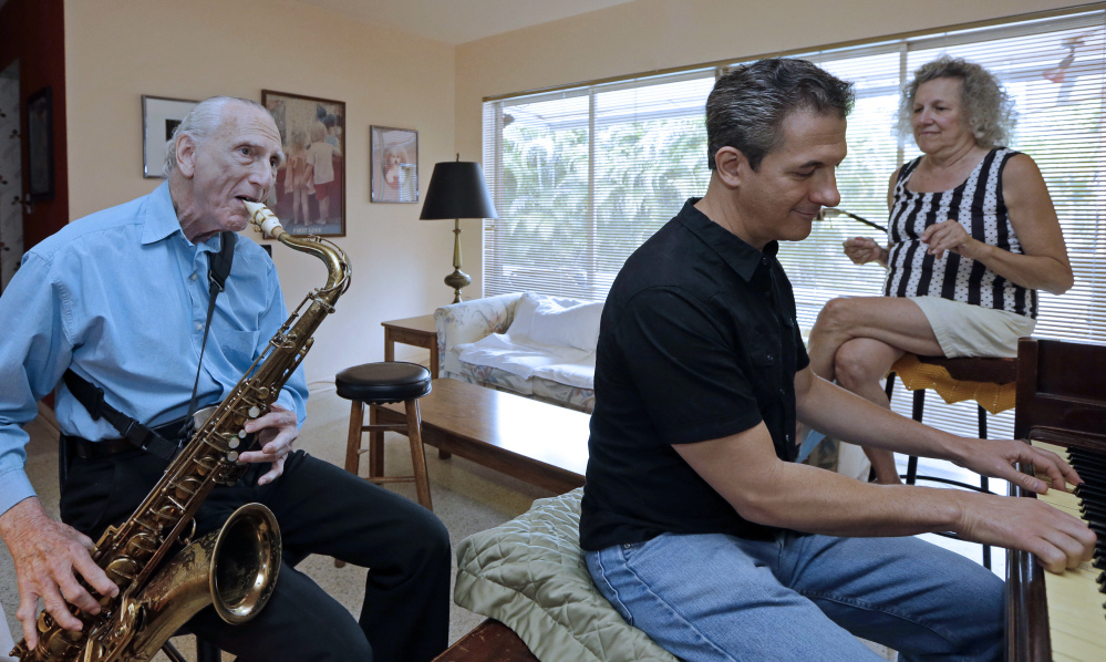 Al Karp, left, plays the saxophone as he rehearses with his son Larry and wife, Saundra, at their home in North Miami Beach, Fla. The trio performs old standards as the Karp Family to ease stress and help raise money to save their home from foreclosure.